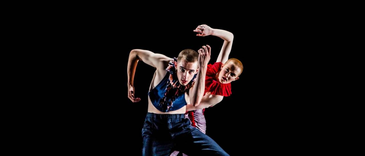2 dancers against a black background, knees bent, one behind the other peeping out the right side.