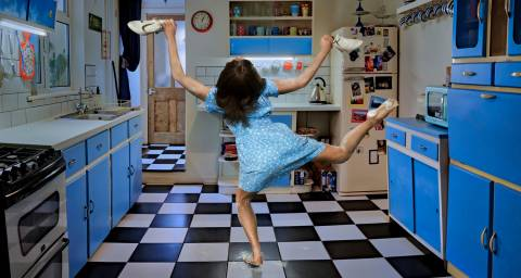 Roots image, dancer in a blue kitchen with back to the camera and legs in the air holding shoes.