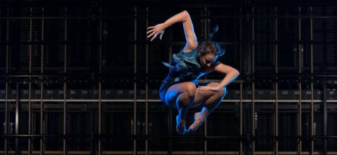Dancer wearinf a blue dress, jumping in the air legs in a ball with one arm at a 90 degree angle