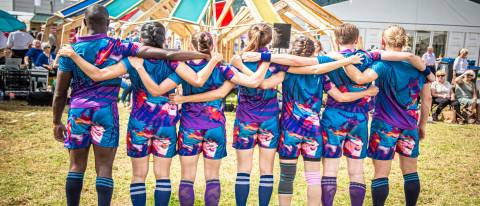 Image of 7 dancers with their backs to the camera, arms linked behind their backs. They are wearing bright coloured sports kits